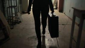 Funcionamientos jovenes de la mujer de negocios lejos con la maleta almacen de metraje de vídeo