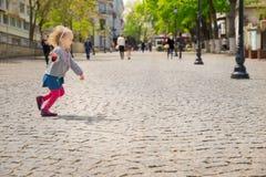 Funcionamientos a lo largo de la calle, adoquines de la niña Imagen de archivo libre de regalías