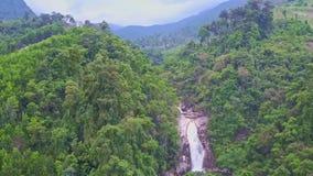 Funcionamientos rápidos del río de la cascada de la visión panorámica entre las colinas verdes