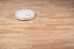 Funcionamientos robóticos del aspirador en piso laminado Economía doméstica elegante moderna de la tecnología de limpieza Con su  fotografía de archivo