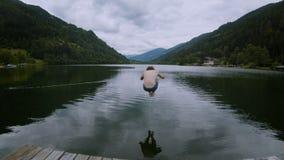 Funcionamientos y saltos del hombre joven en el agua alpina del lago almacen de video