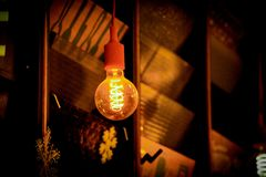 The function of a lightbulb in a dark room. A light bulb shining so strong that you can see the details of the inside Stock Images