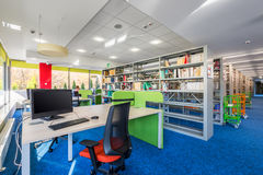 Functional library interior. With wooden desks, office chairs and computers stock photo
