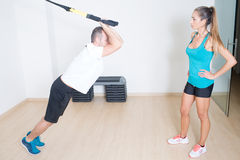 Functional training. Personal trainer helps with functional training exercise Stock Photos