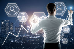 Fund management concept. Back view of young businessman managing abstract business screen on night city background. Fund management concept Royalty Free Stock Photos