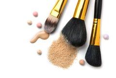 A fundação ou o creme líquido cosmético, pó de cara fraco, várias escovas para aplicam a composição Compõe a mancha e o pó do ocu Imagens de Stock