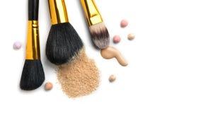 A fundação ou o creme líquido cosmético, pó de cara fraco, várias escovas para aplicam a composição Compõe a mancha e o pó do ocu Imagem de Stock Royalty Free