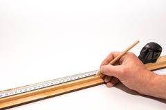 Fundador de imagen, carpintero que marca un pedazo largo de marco con un lápiz fotos de archivo