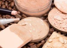 Fundamentmakeupprodukter på kaffebönor Fotografering för Bildbyråer