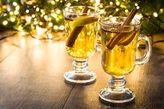 funderad äppeljuice i exponeringsglas, prydnader och julljus på trä Arkivbilder