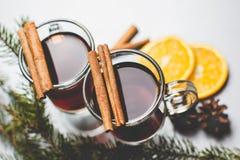 Funderad varm drink för vin med citruns och kryddor i en glass kopp och prydlig filial på en konkret bakgrund Royaltyfri Bild