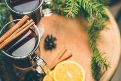Funderad varm drink för vin med citruns och kryddor i en glass kopp och prydlig filial på en konkret bakgrund Arkivbilder