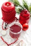 Funderad vin och stearinljus med julpynt omkring Arkivfoto