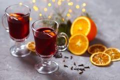 Funderat rött vin med kryddor och apelsinen på mörk bakgrund Värmedrink royaltyfria foton