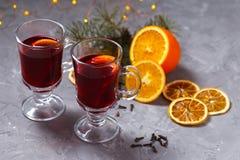 Funderat rött vin med kryddor och apelsinen på mörk bakgrund Värmedrink royaltyfri fotografi
