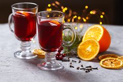 Funderat rött vin med kryddor och apelsinen på mörk bakgrund Värmedrink royaltyfri foto