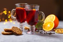 Funderat rött vin med kryddor och apelsinen på mörk bakgrund Värmedrink royaltyfri bild