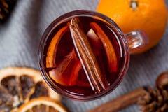 Funderat vin i exponeringsglas med apelsinen och kryddor med den gråa halsduken royaltyfri foto