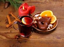 Funderat vin i exponeringsglas med den kanelbruna pinnen, stearinljuset och sötsaker Fotografering för Bildbyråer