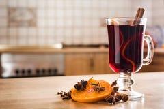 Funderat vin i exponeringsglas med kryddan och frukt på trätabellen i köket royaltyfria foton