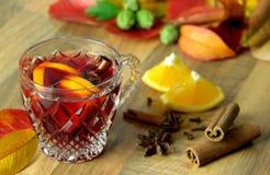 Funderat vin med citrusfrukter, kanel, kryddnejlikor och stjärnaanis Varm kryddig drink höstbakgrundscloseupen colors orange red  Arkivfoto