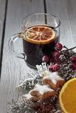 Funderat vin med höfter för kanelbruna pinnar för stjärnor för orange skiva kanelbruna rosa på träbakgrund Royaltyfri Bild
