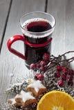 Funderat vin med kanelbruna höfter för kanelbruna pinnar för stjärnor rosa på träbakgrund Royaltyfria Bilder