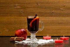 Funderat vin med kryddor på en snöra åtservett Stearinljus i formen av en hjärta, kanelbruna pinnar och ett äpple Fotografering för Bildbyråer