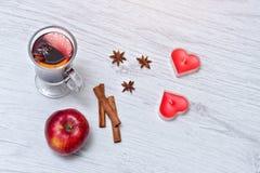 Funderat vin med kryddor på en snöra åtservett Stearinljus i formen av en hjärta, kanelbruna pinnar och ett äpple ljust trä för b Fotografering för Bildbyråer