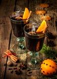 Funderat vin med orange skivor på trä - övervintra värmedrinken Arkivbild