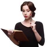 Fundersam affärskvinna med dagboken Arkivfoto