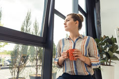 Fundersam affärskvinna på anseende för kaffeavbrott på fönstret Royaltyfri Bild