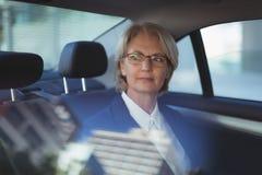 Fundersam affärskvinnaresande i bil Fotografering för Bildbyråer