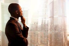 Fundersam affärsman för ung afrikansk amerikan som ser till och med wi Royaltyfri Fotografi