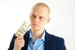 Fundersam affärsman i dräkt på hållande kassa för vit bakgrund Tänka om danandepengar royaltyfri bild