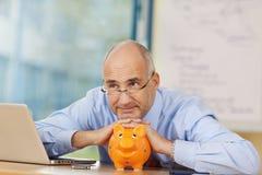 Fundersam affärsman Leaning On Piggybank på skrivbordet Arkivfoto