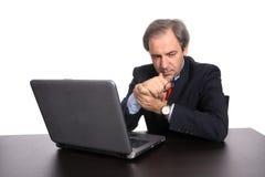 Fundersam affärsman med bärbar dator på hans skrivbord royaltyfri fotografi
