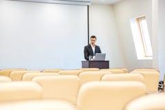 Fundersam affärsman med bärbara datorn i tom konferenskorridor Arkivbilder