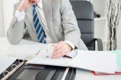 Fundersam affärsman på kontoret Arkivfoto