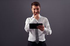 Affärsman som ser PC och att le för tablet Royaltyfri Fotografi