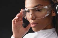 Fundersam afrikansk kvinna som arbetar med hörlurar med mikrofon arkivfoto