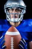 Fundersam amerikansk fotbollsspelareinnehavboll Royaltyfria Bilder