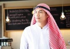 Fundersam arabisk man som framme står på kaffekafét royaltyfri bild