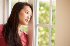 Fundersam asiatisk kvinna som ser ut ur fönster Royaltyfri Bild