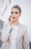 Fundersam attraktiv affärskvinna på telefonen Royaltyfria Bilder