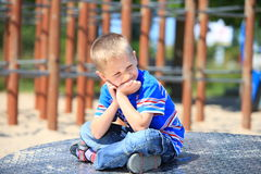 Fundersam barnpojke eller unge på lekplats Arkivfoton