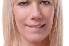 Fundersam blond kvinna som biter hennes kant Arkivfoto