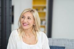 Fundersam blond vuxen kontorskvinna som ser upp Arkivfoton