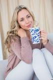 Fundersam blondin på den hållande koppen kaffe för soffa royaltyfri foto