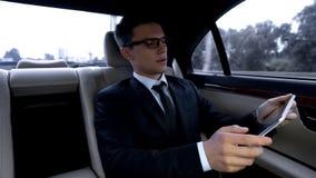 Fundersam chef som arbetar på minnestavlan som rider i lyxig bil genom att använda tid i trafik arkivbild